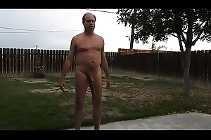 A stripped old man peeing uppish back patio.